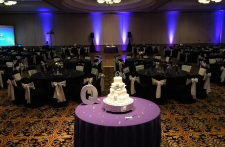 Ballroom wedding reception with spotlighted wedding cake