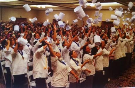 Newly graduated chefs throwing chef hats