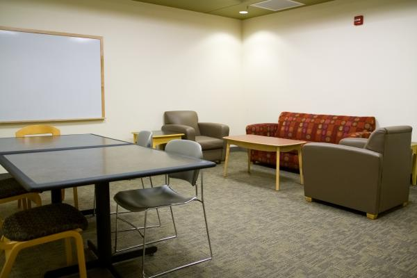 A Medium size room with a whiteboard, couches, and tables.