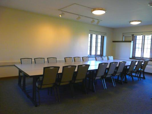 Half of the conference room set with seating for 18