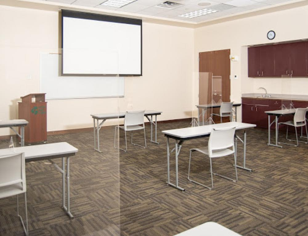 Socially distanced classroom set up with sneeze guards.