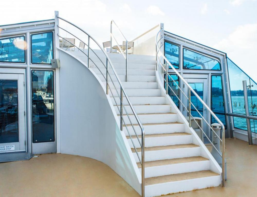 Stairs that go from dining deck to rooftop deck on a Hudson Harbor yacht