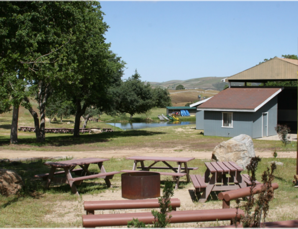 View of outdoor meeting space, Upper Dorm, and pond.