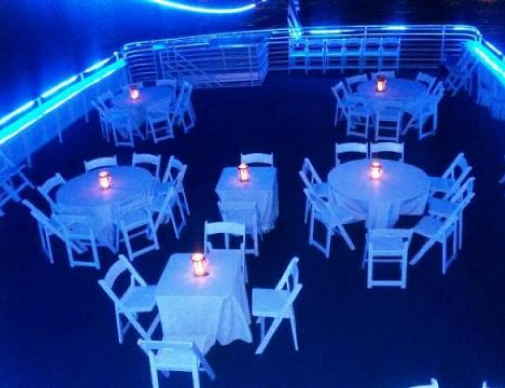 Outdoor rooftop deck with linen-covered tables, white garden chairs, & illuminated lanterns